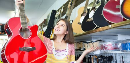 Brunette female choosing acoustic guitar in music instruments store