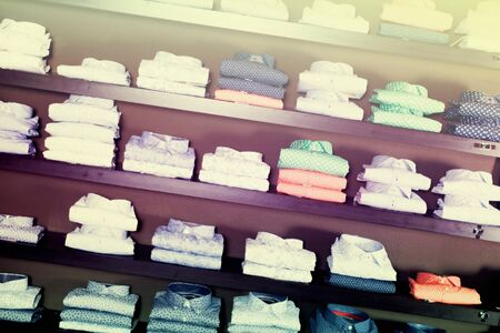 row of shirts on shelfs in male clothing store