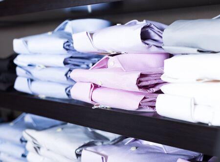 row of shirts on shelfs in men showroom