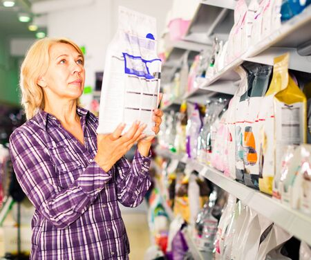 Portrait of mature woman purchasing pet food in petshop Imagens