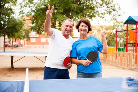 mature couple showing victory near table tennis at outdoor
