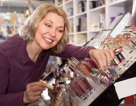 mature interested woman choosing lip plumper on display and smiling Imagens