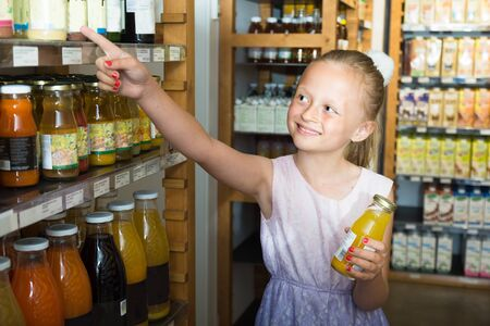 blonde girl posing with bottle of juice in supermarket