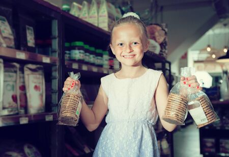 blonde girl posing with cookies in supermarket Imagens