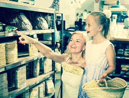 young mother with daughter buy corn cakes in store Imagens