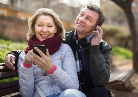 Happy mature couple talking on the phone on a park bench Stockfoto