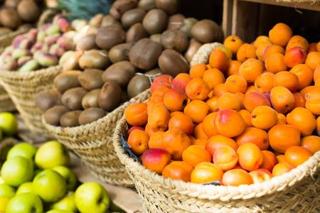 mature appetizing apricots in wicker baskets on counter in market