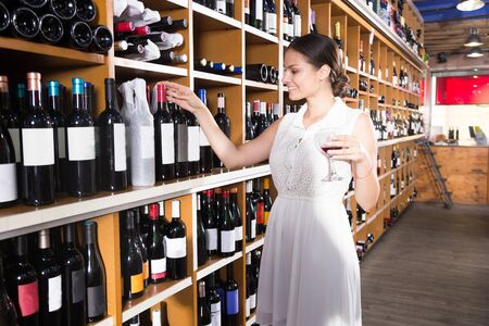 girl in trying red wine at a wine store