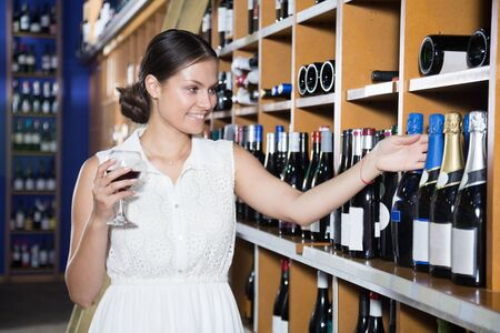woman chooses wine in department of supermarke
