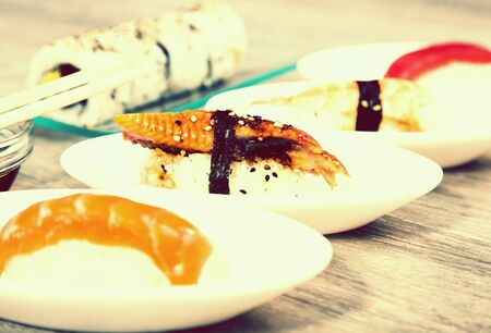 four kinds Nigirisushi on oval saucers and Uramaki. focus on unagi
