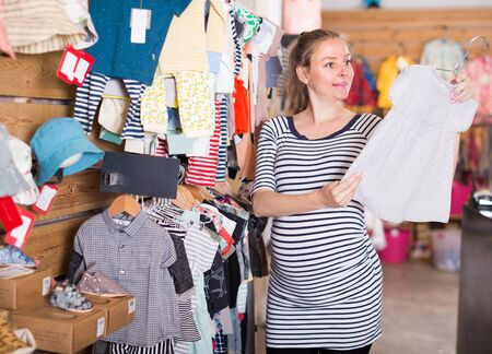 european expectant mother shopping in clothing store for babies