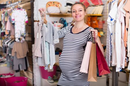 happy pregnant woman with shopping bags in clothing store on shopping