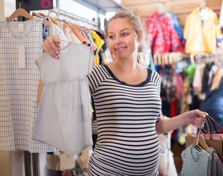 Female Pregnant Buyer In striped tunic Reviews Newborn Dress in the Store