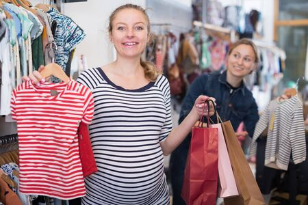 pregnant woman in striped tunic chooses striped shirt in clothing shop Stockfoto