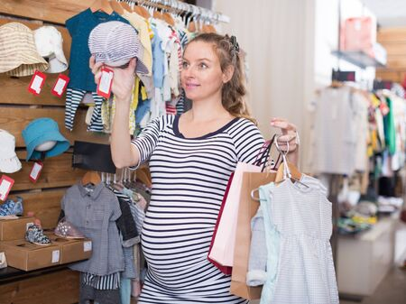 pregnant woman in striped tunic chooses hat for the baby in boutique