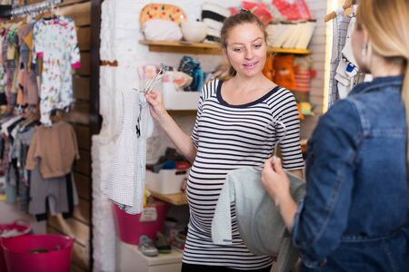 pregnant woman in striped tunic communicates with seller in clothing store for babies