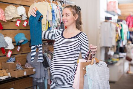 pregnant woman in striped tunic chooses clothes for boy in boutique