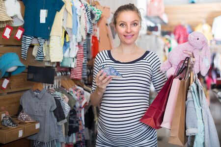 pregnant woman in striped tunic chooses shoes for the baby in boutique Stockfoto
