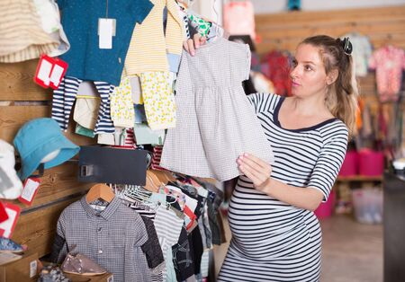 Pregnant woman in a striped tunic chooses clothes for the future child in store