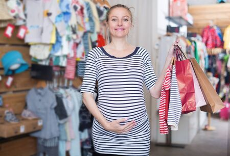 pregnant woman In striped tunic with shopping bags in clothing store