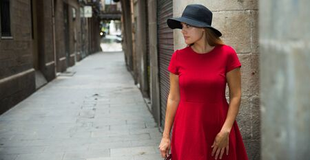 beautiful young girl in red dress walks through the old European streets 免版税图像 - 130353766