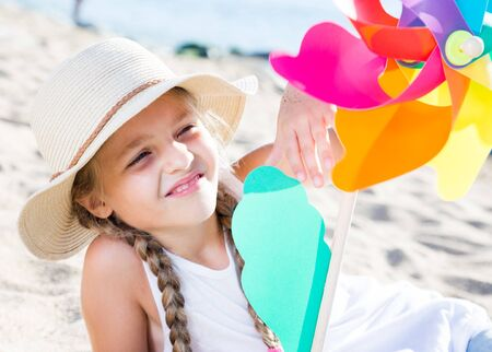 baby girl with windmill on sea in summer