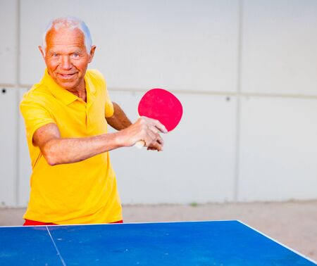 Happy mature man playing table tennis