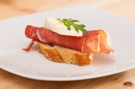perfect sandwich made with rye bread cheese and Parma ham on a white plate Stock Photo