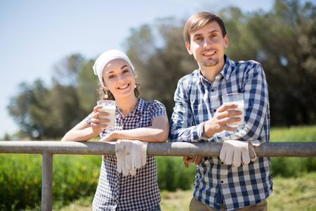 young country couple of farmers drink milk in field near fenc
