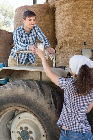 young country woman give to man tractor driver glass of milk on farm Stok Fotoğraf