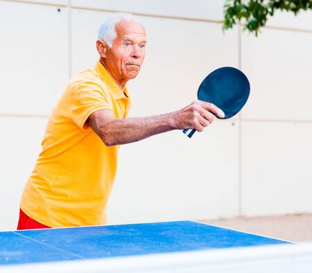 mature man in yellow Tshirt playing ping pong outdoors