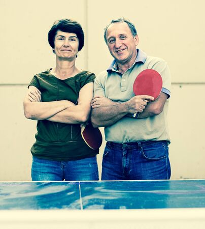 portrait of elderly posing couple with rackets for table tennis 写真素材