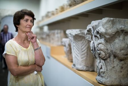 female collector evaluates the exhibition in historical museum