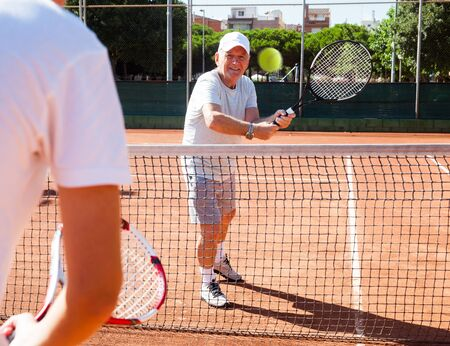mature man playing at tennis court 写真素材