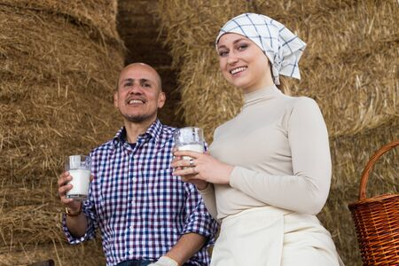 couple of farmers drinking milk in hayloft on farm Фото со стока