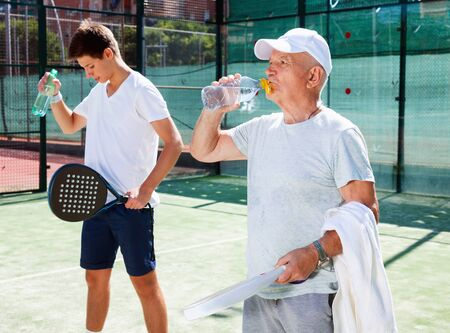 Glad cheerful positive mature man and young man drink water on padel court