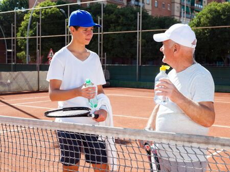 older man and young man talking on court playing tennis 写真素材