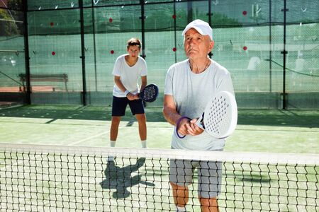 Glad cheerful positive  mature man and young man playing padel court