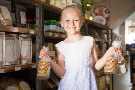 blonde girl posing with cookies in supermarket Banco de Imagens