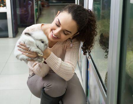 happy girl customer watching fluffy chinchilla in petshop