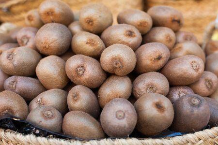 ripe kiwi in wicker baskets on counter market Фото со стока