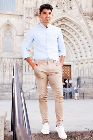 ordinary young European guy in blue shirt walking around city