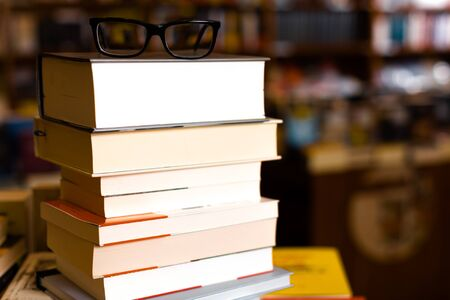 glasses on top of different art books lying on table in school library