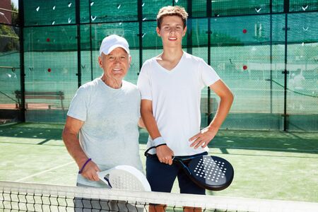 Glad cheerful positive  senior man and young man posing on padel court Reklamní fotografie