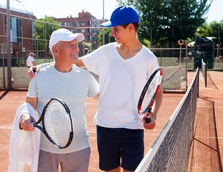 tennis players of different generations talking on court playing tennis Banco de Imagens