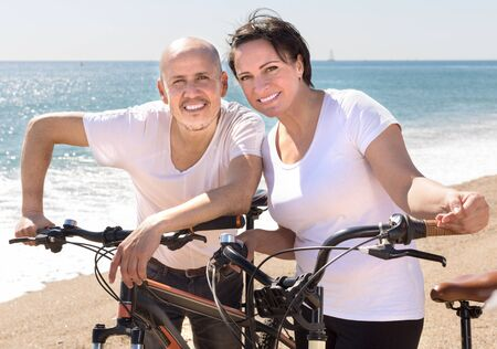 elderly man with a woman in white shirts walking with bicycles on the sand in summer