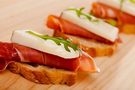 perfect sandwich made with rye bread cheese and Parma ham on a wooden tabletop Stock Photo