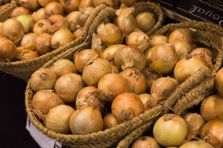 Mature bulb onion in wicker baskets on market counter