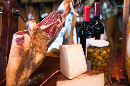 Still life with jerked iberic jammon of bacon with wine, cheese and olives