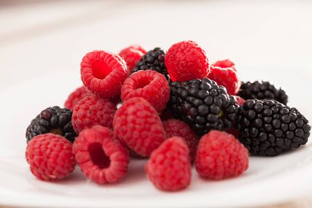 handful of fresh raspberry and blackberry berries on white background Stock fotó